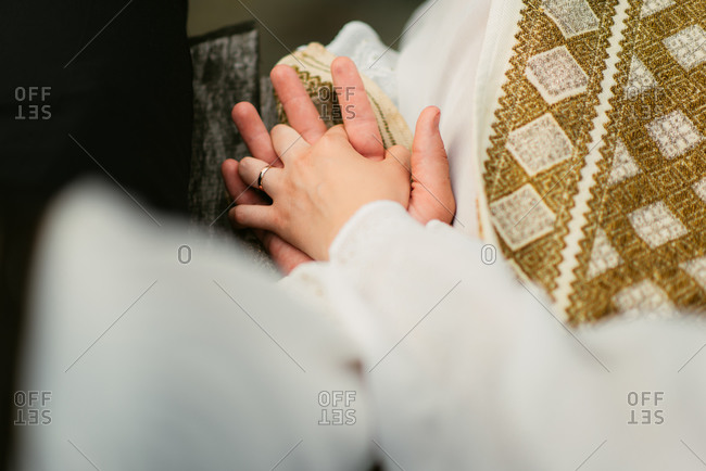 Priest joining couple's hands during wedding ceremony
