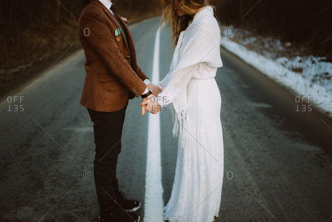 Bride and groom holding hands in road in winter