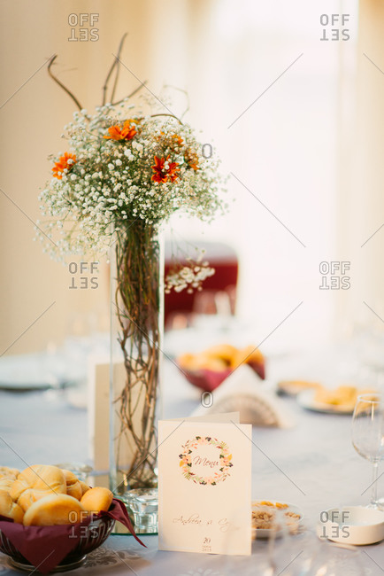 Bouquet of flowers and table set for wedding reception