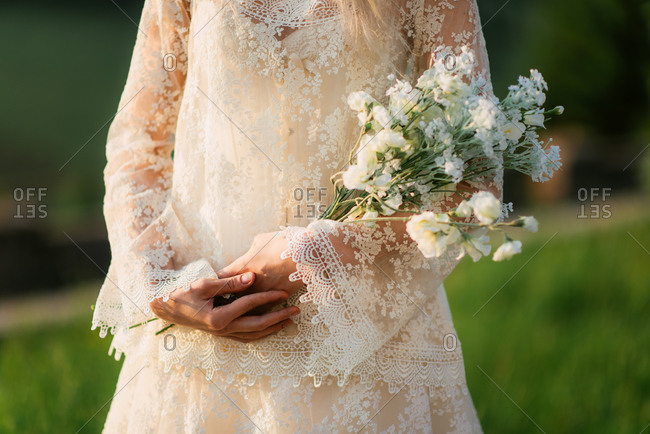 Bride standing holding loose bouquet of flowers outside