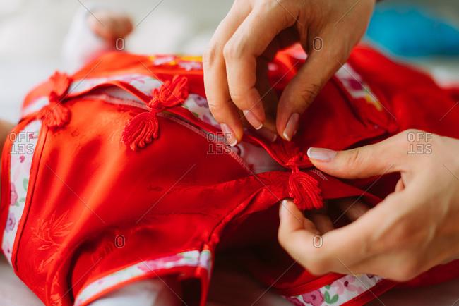 Woman buttoning up kimono shirt on baby