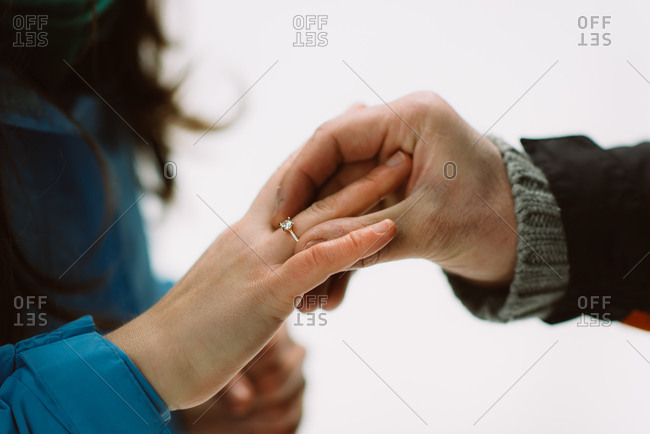 Man putting engagement ring on woman's hand in winter