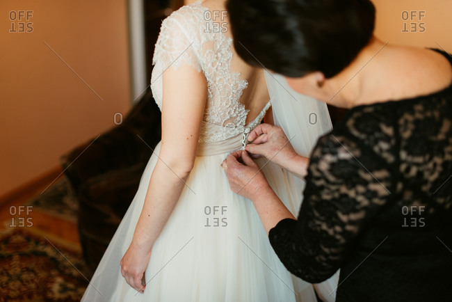 Woman helping to button on bridal gown