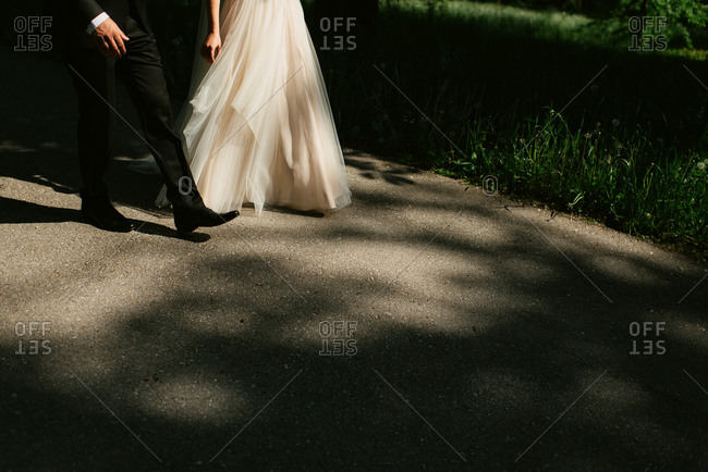 Bride and groom walking on rural path together