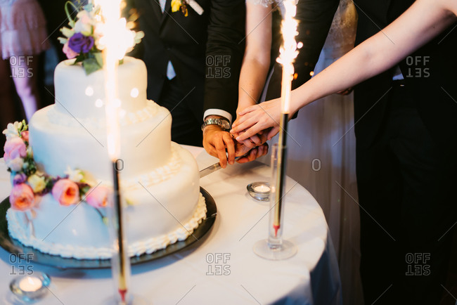 Two couples cutting cake during wedding reception