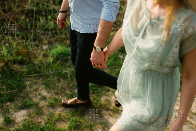 Stylish couple walking hand in hand in field