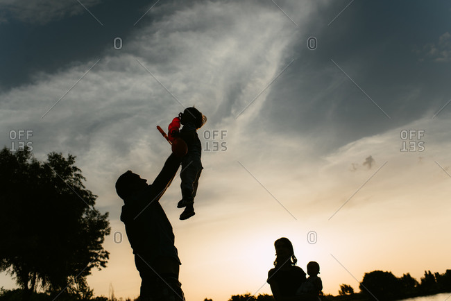 Silhouette of family playing together in rural setting