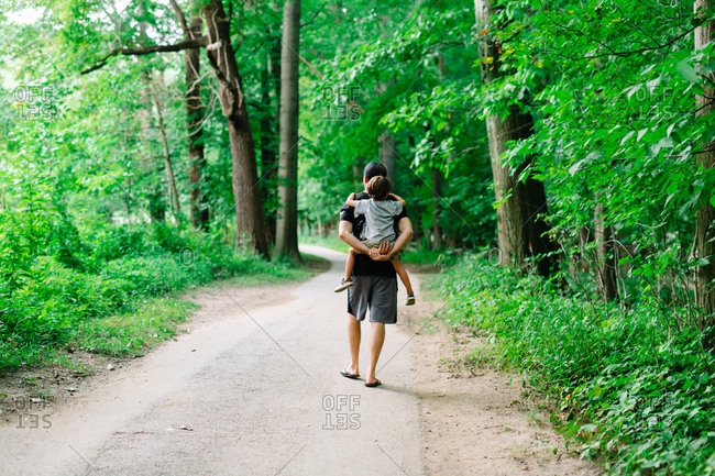 Father walking on a nature trail carrying his son on his back