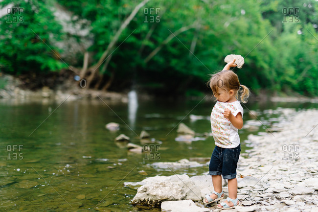 Little girl throwing a large stone into a river
