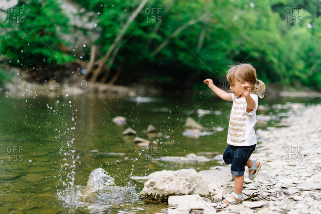 Little girl tossing a rock into a river
