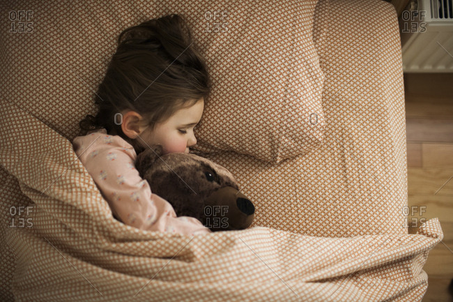 Girl holding stuffed bear asleep under covers