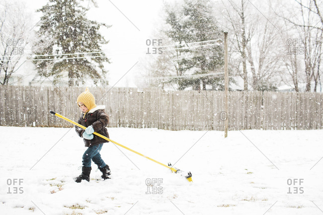 Girl dragging a broom around snowy yard
