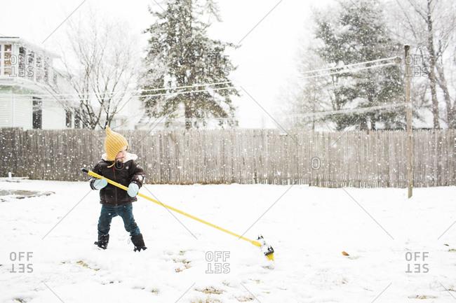 Girl dragging a broom through snowy yard