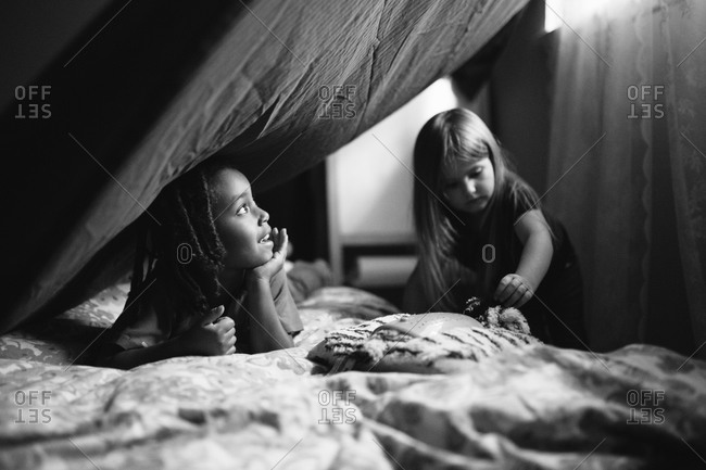 Two young girls playing in blanket tent in bedroom