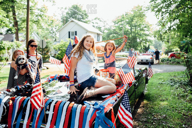 Children playing on the back of a classic car decorated for Independence Day parade