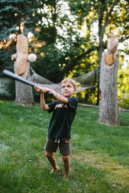 Boy swinging bat to hit a wiffle ball in backyard