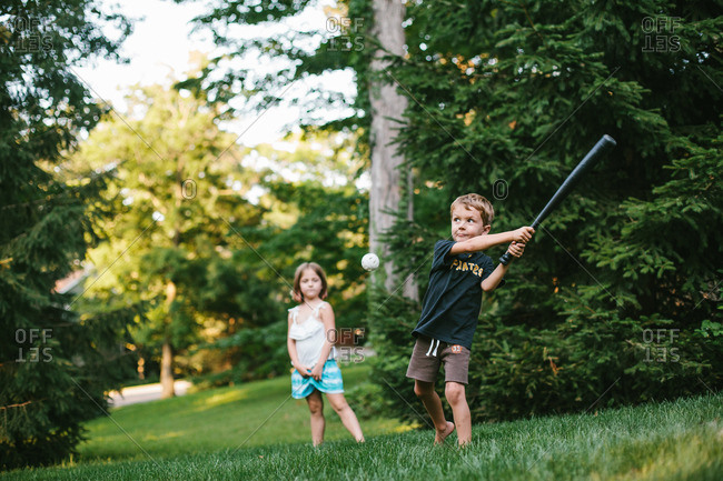 Boy and girl playing wiffle ball in backyard