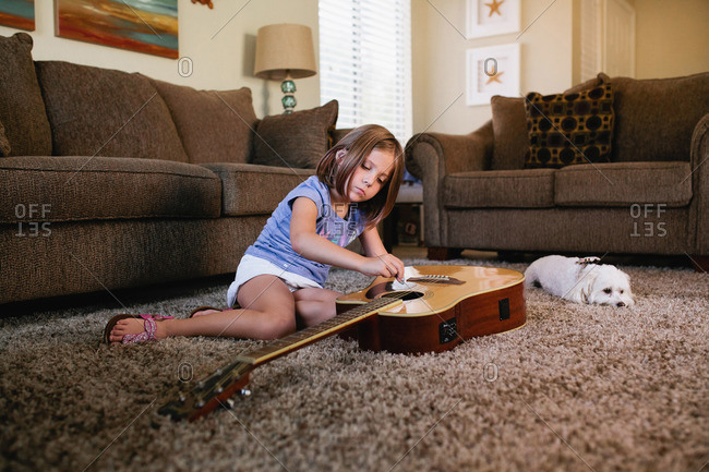 Young girl playing guitar on carpet with white poodle lying nearby