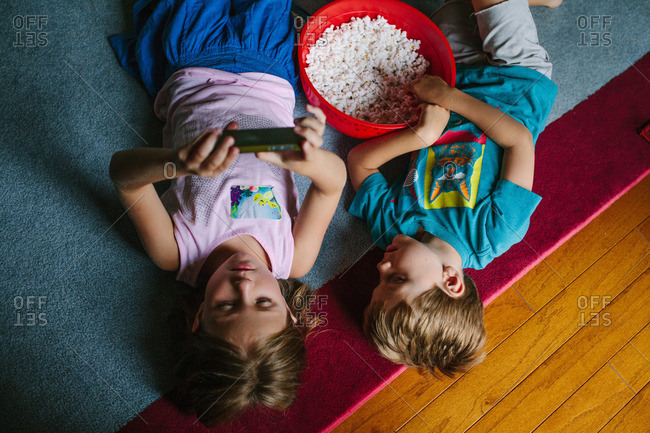 Overhead view of two young children lying on floor with popcorn watching a smart phone