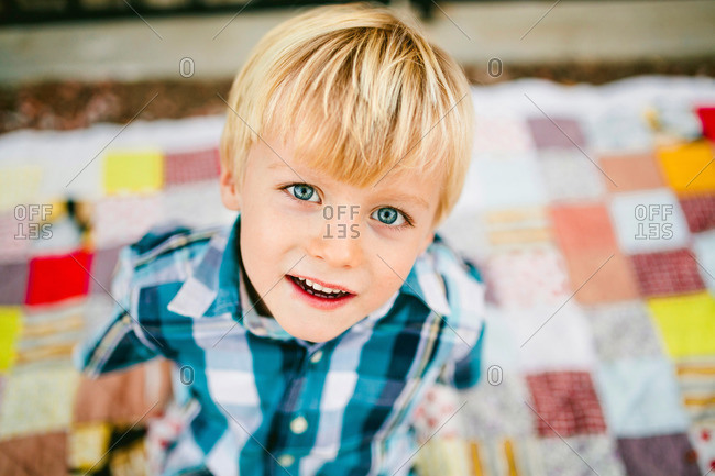 Cute blond boy in plaid shirt sitting on a quilt