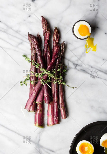 Overhead view of purple asparagus on white marble with thyme and soft boiled egg