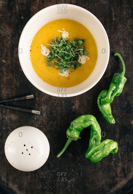 Overhead view of a dish of yellow pureed soup garnished with microgreens and cream