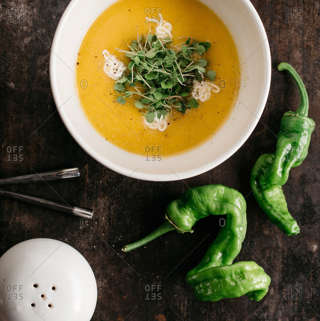 Bowl of yellow pureed soup garnished with microgreens and cream