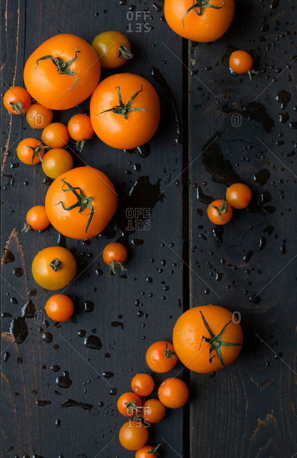 Arrangement of fresh orange tomatoes on black wooden table