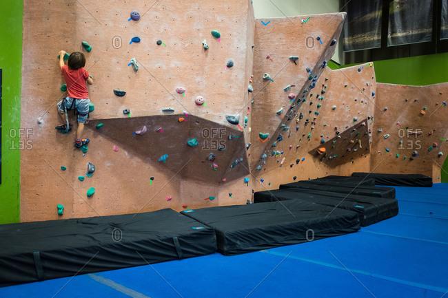 Little boy climbing on an indoor rock wall