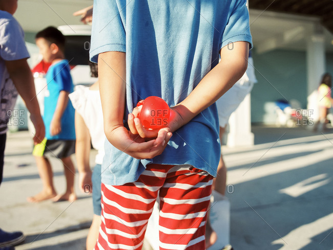 Boy holding a water balloon behind his back