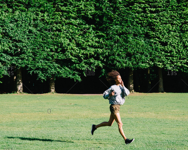 Girl running across a lawn listening to music