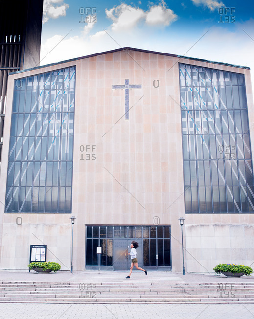 Girl running in front of a modern church in Malmo, Sweden