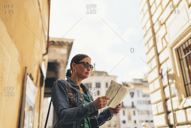 Woman reading map on the streets of Rome, Italy