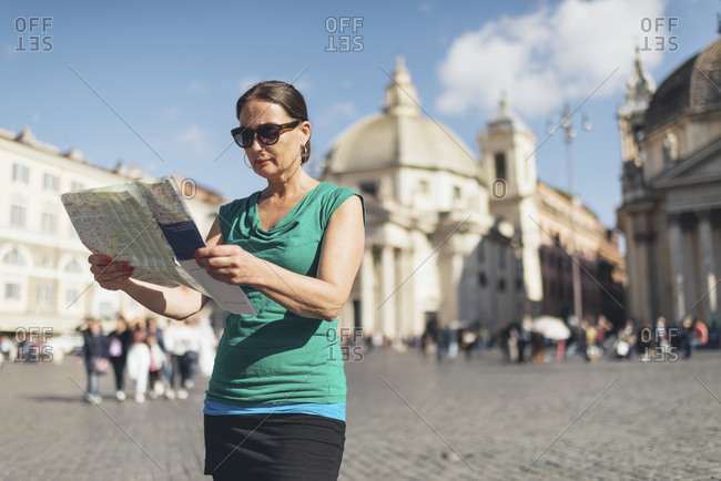 Woman reading map in Rome, Italy