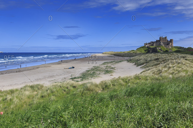 Bamburgh Castle across the dunes, early Summer afternoon, Northumberland, England, United Kingdom