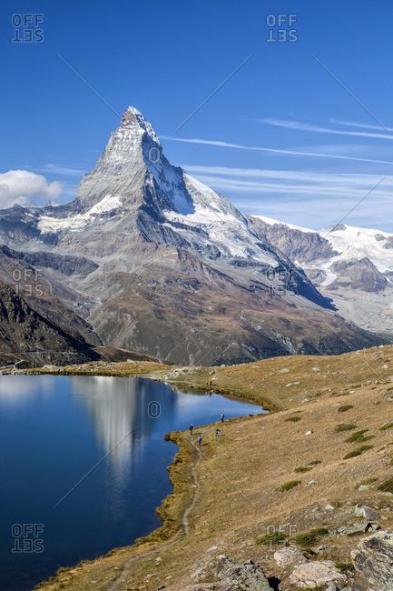 Hikers walking on the path beside the Stellisee with the Matterhorn reflected, Zermatt, Switzerland