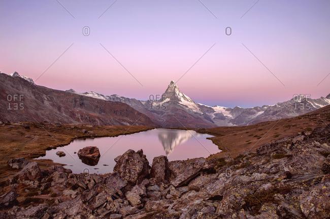 Pink sky at sunrise on the Matterhorn reflected in Stellisee, Zermatt, Switzerland