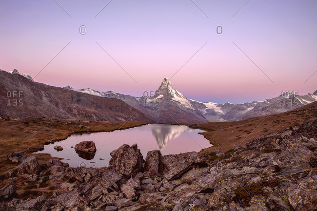 Pink sky at sunrise on the Matterhorn reflected in Stellisee, Zermatt, Switzerland