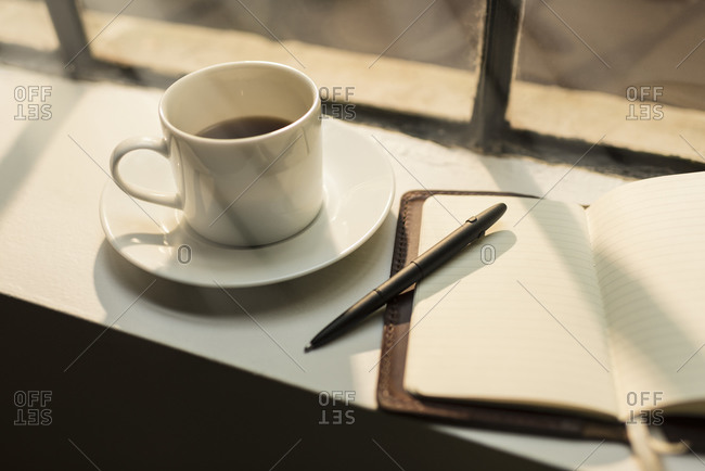 Blank leather journal and coffee on windowsill