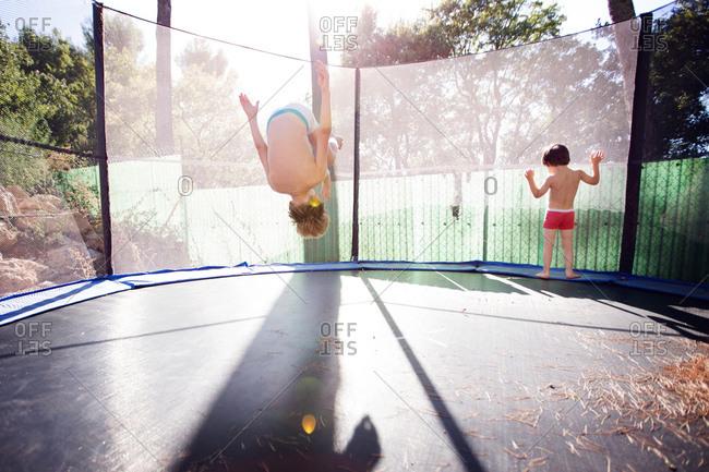 Boys doing flips on a trampoline