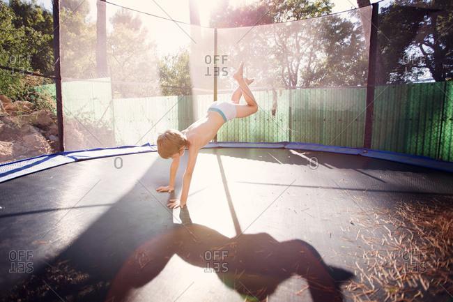 Boy doing acrobatics on a trampoline