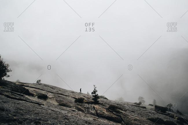 Man walking down a foggy mountain slope