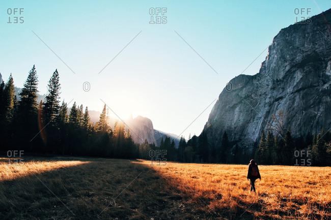 Woman walking through a field near mountains