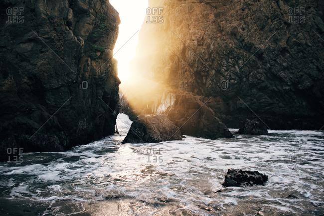 Sunlight shining between seaside cliffs