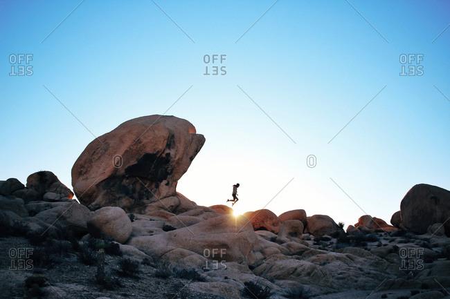 Woman leaping across rocks in a desert