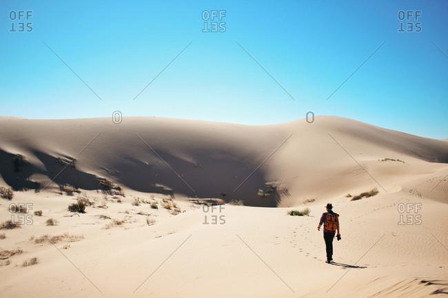 Man walking toward dunes in a desert