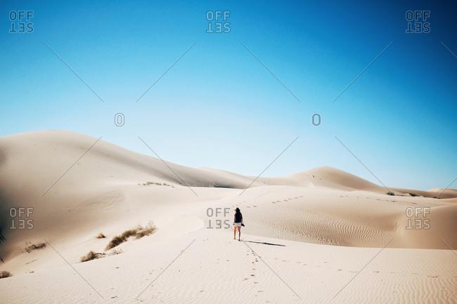 Woman walking across desert dunes