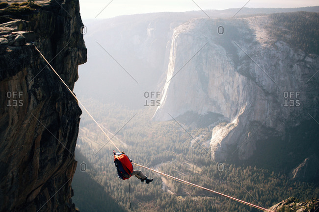 Man crossing a mountain gap using a tightrope