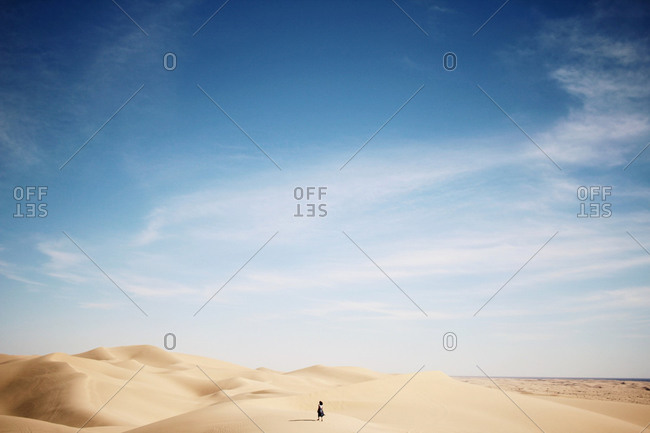 Woman walking across sand dunes in a desert