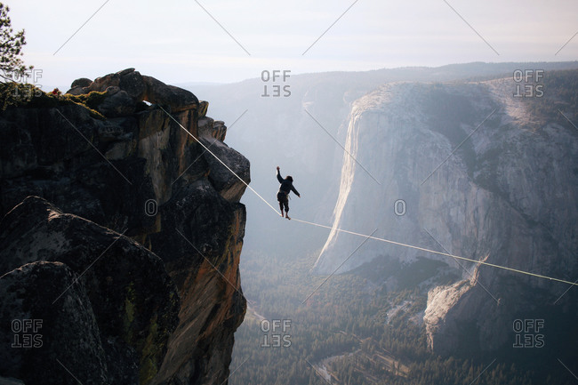 Man walking on a tightrope stretched across a mountain gap